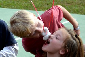 boy and girl biting donuts on a string